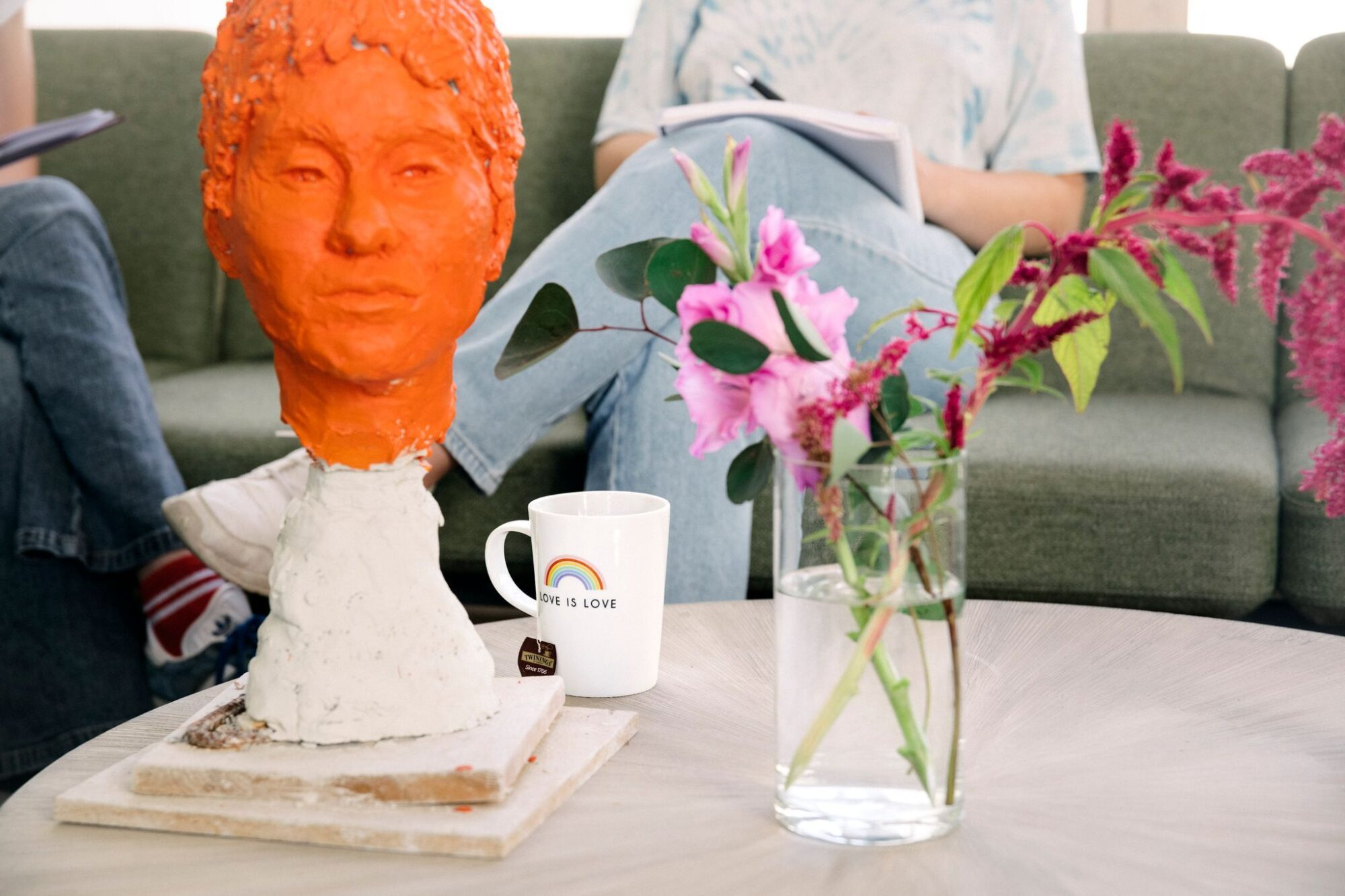 Bord med kopp, blomster og skulptur