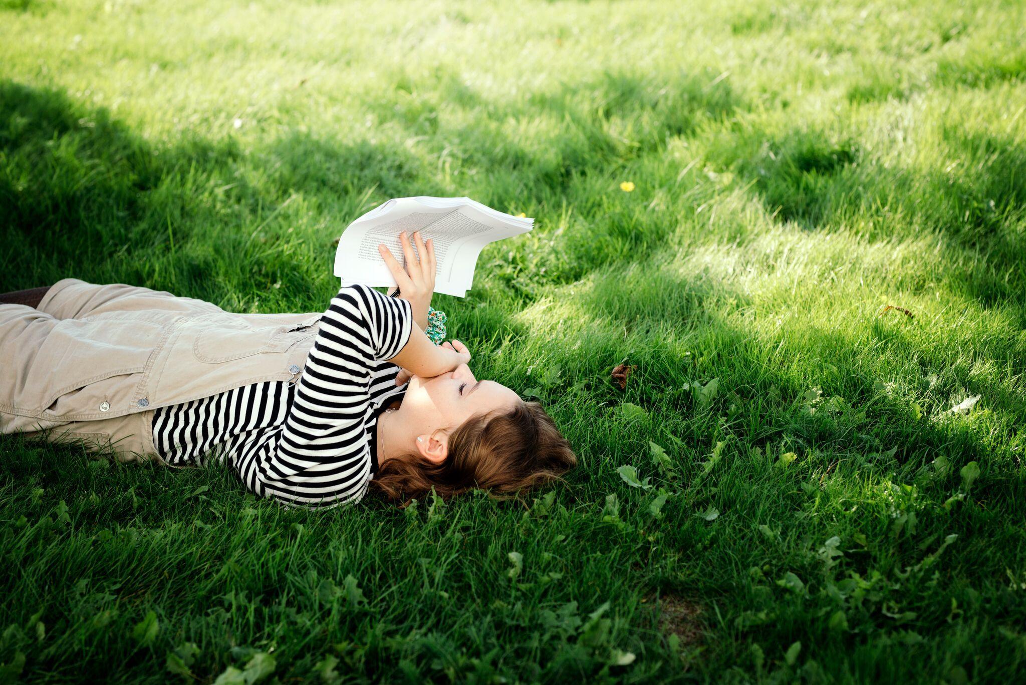 Jente leser i hagen